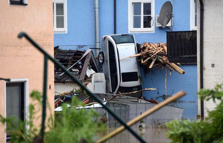 In this June 1, 2016 photo a car is squeezed between houses of Simbach am Inn, southern Germany, after the small town was hit by flooding. Several people have died. (Tobias Hase/dpa via AP) Photo: Tobias Hase, AP / dpa