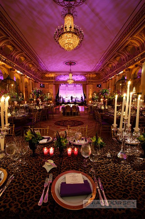 Wedding reception tables are covered in cheetah tablecloths and topped with votives and crystal candelabras.