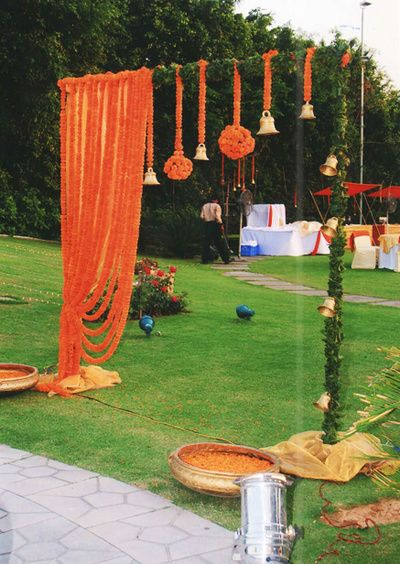genda flowers and balls , bells and flowers , orange gold and green entrance decor , simple yet pretty  gateway