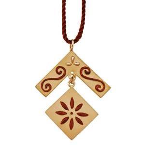 Pendente in oro sabbiato con particolari in rilievo smaltati di rosso. Cordoncino rosso in seta.