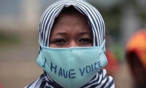 A female Indonesian human right activist in Jakarta wears a hijab and a large nose and mouth mask on which she has written 'I have voice'
