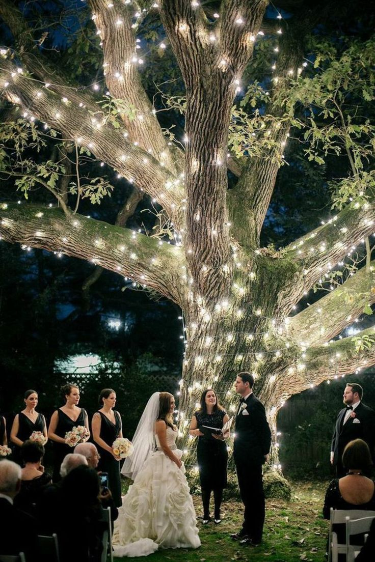 a magical, romantic night wedding ceremony under illuminated tree