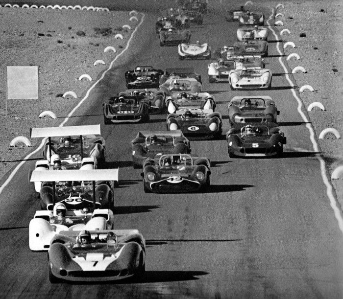 John Surtees in Car 7, a Lola T70, leads the Las Vegas Can-Am race in 1966. Just behind Surtees is Jim Hall in a Chaparral 2E and Car 98, which is Parnelli Jones in another Lola T70. Behind Parnelli Jones is Phil Hill in another Chaparral 2E who is being challenged by Jackie Stewart's Lola T70, Car 43. Other cars behind Hill and Stewart are George Follmer's Lola T70 (Car 16), Bruce McLaren's McLaren M1B (Car 4), Chris Amon (Car 5) in another McLaren, Mark Donohue's Lola T70 (Car 6),