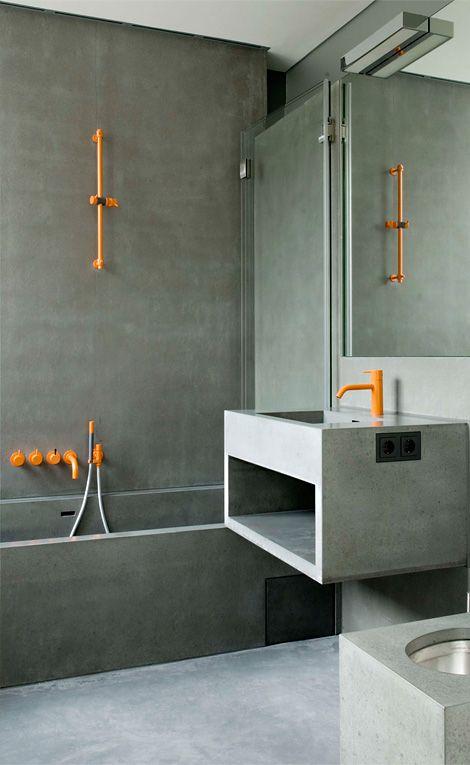 Fantastyczne połączenie: płytki imitujące beton, pomarańczowe baterie, a wszędzie minimalistyczne wykończenia.