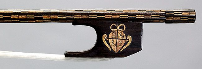 Violin bow attributed to the workshop of Antonio Stradivari, Cremona, c1700. This bow is one of only two bows attributed to the workshop of Antonio Stradivari. It has a fluted stick, probably inlaid later in the mid-18C in Spain, with colored fruitwoods. This side of the bow's later mahogany frog (made before 1788) is inlaid with the royal coat of arms of Charles IV (r.1788-1808)