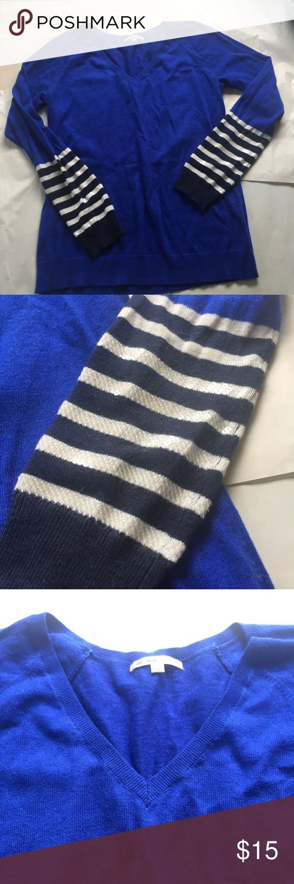 GAP Blue and White Sweater with Sequin Details Gorgeous royal blue colored GAP sweater with a flattering v neck. The sleeve cuffs are white and navy blue stripes. The white stripes have really nice white sequins on the white stripes. 57% nylon, 28% wool, and 15% acrylic.   same or next day shipping on all orders (except weekends)make me an offer! GAP Sweaters V-Necks