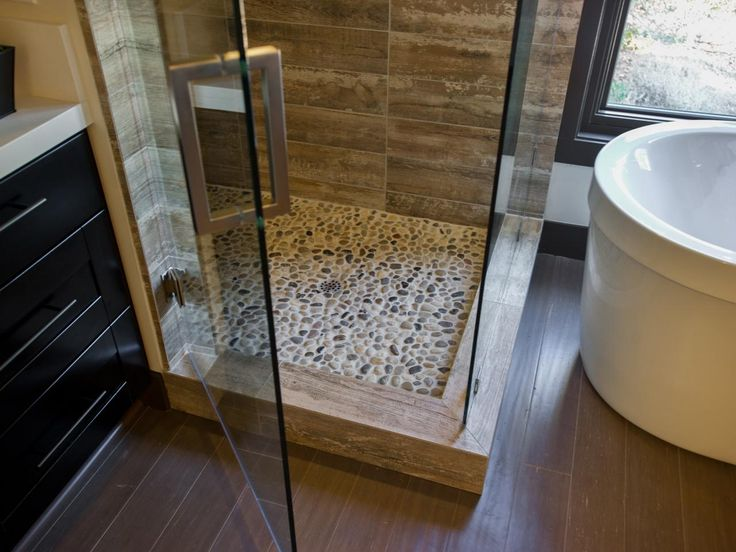 Grouted pebble tile in a range of warm neutrals makes up the floor of the stand-up shower.