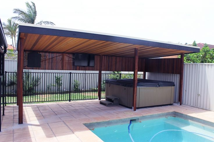 Pergola fit-out with dart board, TV, and spa beside the pool.