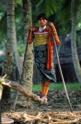 Cary Wolinsky     San Blas Islands, Panama. Cuna Indian woman wearing a mola (appliqué blouse) works a traditional sugarcane press.