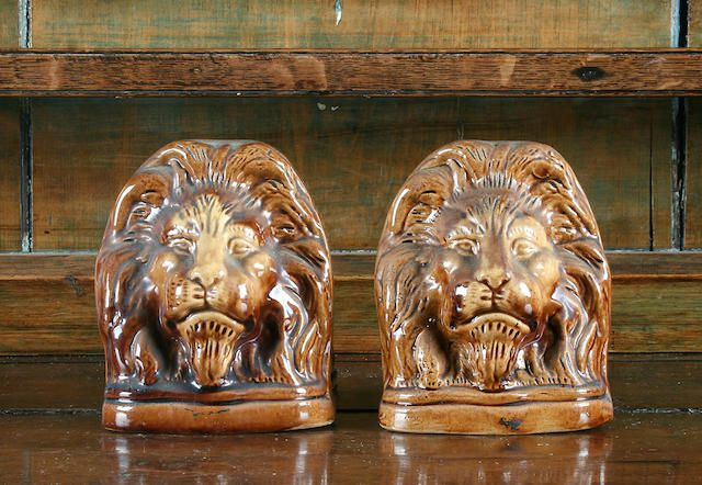 A pair of stoneware sash window stops, circa 1860 Stylistically modelled as lion heads and decorated with a treacle glaze,