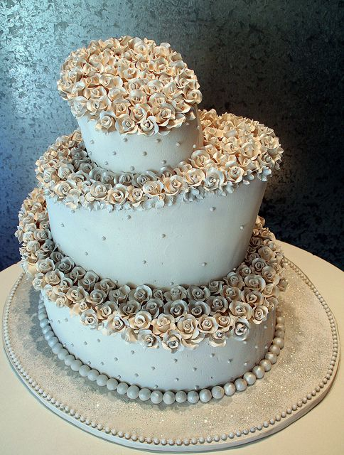Nice kind of simple cake decorated with many small gum paste flowers and also decorated with small uniform placed with dots on the side