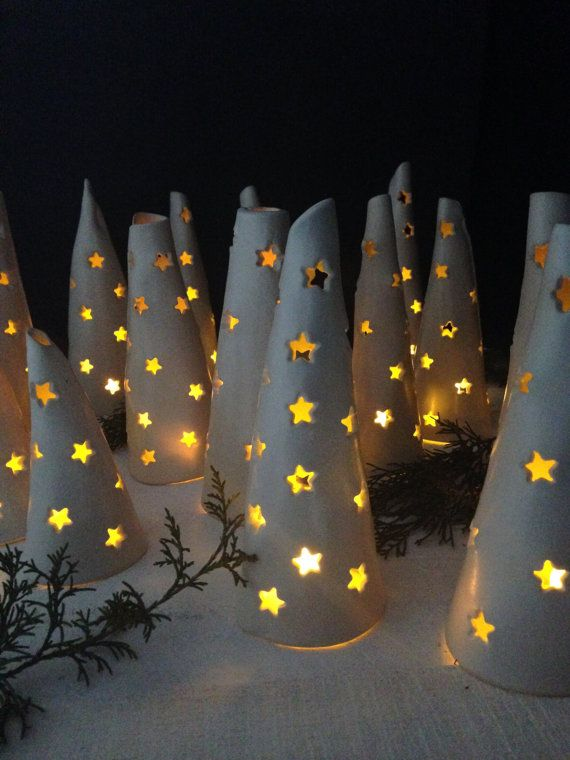 This artfully handcrafted cone tree luminary will add beauty and shine to any decor, in any season. From the white stoneware clay and white satin glaze finish, to the hand cut stars, each tree is individual in design. Your tree will be thoughtfully selected for you, and will arrive with an LED tea light for added sparkle, or you can also use a candle tea light. A truly wonderful gift for anyone.  Approximate size: 7 inches tall