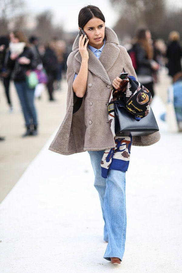 """ラグジュアリーなアイテムをカジュアルシックに着こなすのは、デュマの得意技。3月のパリコレ会場では、スキンカラーのリッチなムートンケープに、B.D.シャツとフレアデニムを合わせて、エレガントな上級スタイルでお出まし。「エルメス」の大判スカーフとバッグ""""バーキン""""を持ちこなす姿もエフォートレス!"""