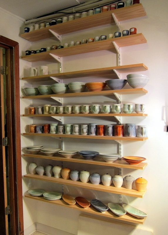 shelves full of pottery, warm out of the kiln