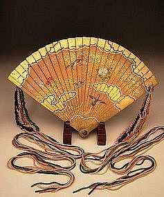 """Japanese Edo Period hand painted wooden fan with silk tassels. This wonderful and rare fan is beautifully hand painted with birds and flower on the front and abstract butterflies and bamboo leaves on the back. Each side has wonderful gold leaf design. The fan measures 11 7/8"""" tall, 18 1/2"""" wide when opened and 2 1/4"""" thick. The wood portion is from the Edo Period and the silk tassels have been replaced in the early 20th century."""