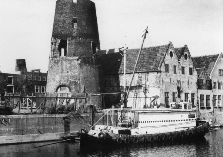 Restant van de molen De Distilleerketel aan de Achterhaven, gezien vanaf het terrein van de H.E.T. aan de Waaldijk. Op de achtergrond de stomp van de moutmolen Het Vertrouwen aan de Schans.      2 oktober 1973