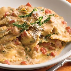 Tusccan pasta  1 (20-oz.) package refrigerated four-cheese ravioli* 1 (16-oz.) jar sun-dried tomato Alfredo sauce $ 2 tablespoons white wine $ 2 medium-size fresh tomatoes, chopped** $ 1/2 cup chopped fresh basil 1/3 cup grated Parmesan cheese