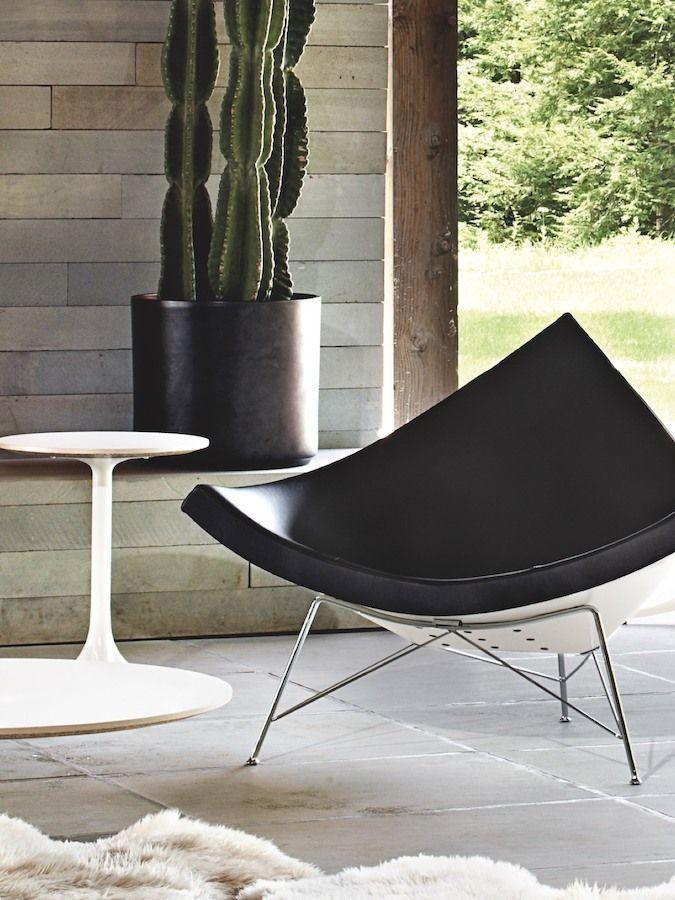 A Black Leather Nelson Coconut Lounge Chair On An Outdoor Patio George Nelson Cadeiras Design De Produto