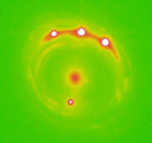 Imagem em raio-x da lente gravitacional de RXJ 1131-1231. Ao centro, a galáxia que serve como lente. Os quatro pontos ao seu redor formam o quasar pesquisado, que apresenta fortes indícios da existência de planetas em seu interior. [Imagem: Universidade de Oklahoma/divulgação]Usando uma galáxia intei