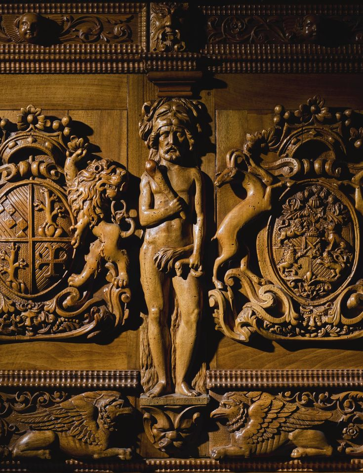 A Swiss carved walnut armorial cabinet, probably Basel, 17th century  the upper section with egg-and-dart formation above two frieze drawers, the two doors with coat-of-arms flanked by three supporting figures, including Hercules with the lion's hide holding a club in his left hand, a snake in his right, the lower part with two long frieze drawers above two ornate doors with Melusine depicted as half woman, half fish, the panels flanked by figures of Adam and Eve