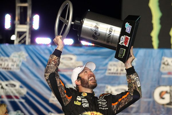 Martin Truex Jr., driver of the #78 Bass Pro Shops/Tracker Boats Toyota, celebrates with the race trophy after winning the Monster Energy NASCAR Cup Series Championship and the Monster Energy NASCAR Cup Series Championship Ford EcoBoost 400 at Homestead-Miami Speedway on November 19, 2017 in Homestead, Florida.
