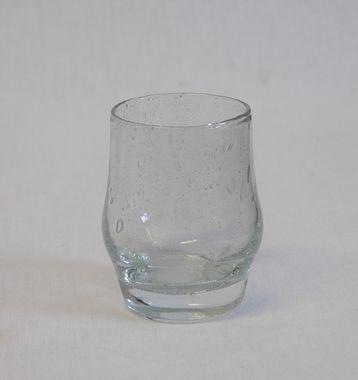 Benny Motzfeldts farrisglass/ drikkeglass JEPPE, produsert 1967 (-70) på Randsfjord Glassverk AS. Klokkeformet med rett oppadgående kant. Luftblærer i glasset (tilsiktet). Mål: Høyde: 9 cm. Diameter: 6 cm. Farge: Klar glass med en svak gråfarve. Inventarnr.: HF-15099. Institusjon: Hadeland Folkemuseum
