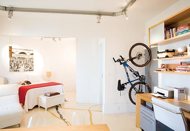 Como se fosse uma peça decorativa, a bicicleta fica presa por ganchos em um painel de aço