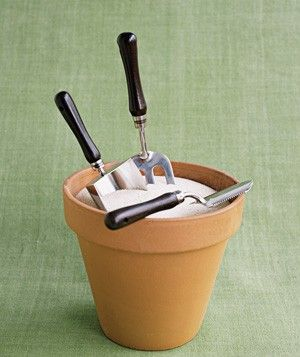 Flower pot with builders sand and mineral oil to hold garden tools and keep from rusting. <3 this idea!