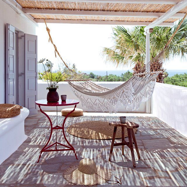 Protégée par un toit de canisses, cette terrasse de l'hôtel San Giorgio est une invitation à la détente et à la contemplation. Comme toutes les autres terrasses, elle est aménagée de mobilier artisanal fabriqué en Grèce, au Mexique, au Brésil ou Espagne. Le sol est ponctué de coussins et de tapis d'herbes tressées fabriqués en Espagne. Le grand hamac réalisé au Brésil invite à admirer le paysage confortablement installé.