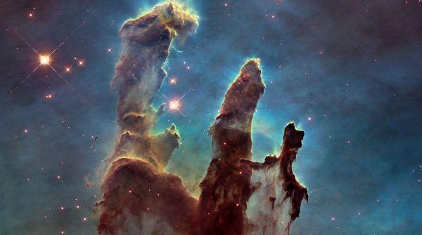 """La Wide Field Camera 3 di Hubble immortala le colonne di gas e polvere che formano i cosiddetti """"Pilastri della Creazione"""", nella Nebulosa Aquila, tra gli oggetti più famosi e affascinanti ripresi dal telescopio spaziale. I diversi colori riflettono le emissioni di diversi elementi chimici: blu per l'ossigeno, arancione per lo zolfo, e verde per azoto ed idrogeno"""