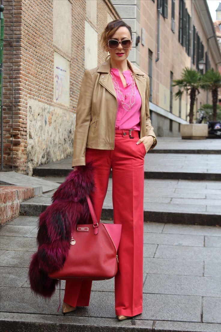 Pantalón en rojo, bolso en rojo y Rosa, chaleco de piel en fucsia, camisa en rosa, cazadora en piel tostada, pelo en coleta y ondas, gafas en cuadrado en blanco