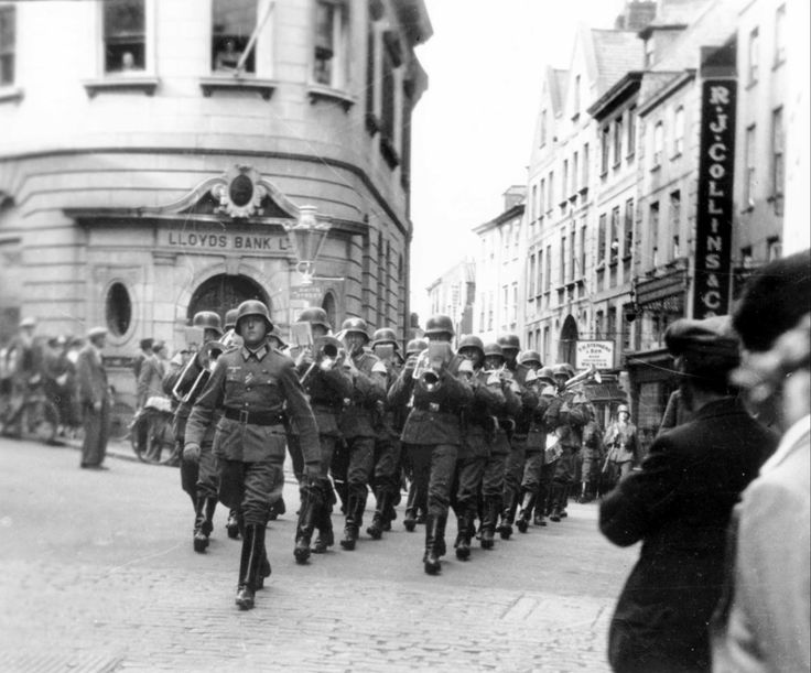 German Army band marching up the High Street of St Peter Port, Guernsey - c. 1940.  For most of World War II, the British Bailiwick in the Channel was occupied by German.