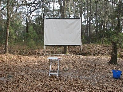 Here is a plan for an outdoor projector screen.... gives an idea as to how to do your own. The site states with research there are alternative ideas for screen material that are even cheaper!