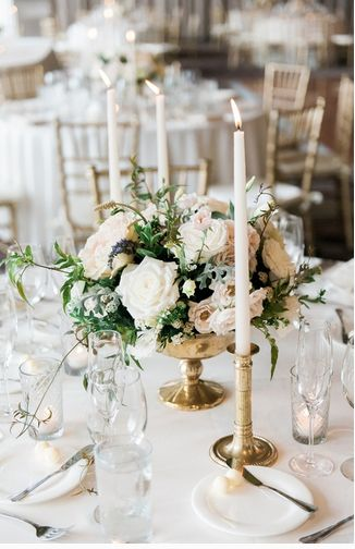 Clean and elegant Idea but too simple? Round tables will a small floral arrangement surrounded by three to four brass candlesticks at various heights. Small votive candles in clear glad will be placed in between.