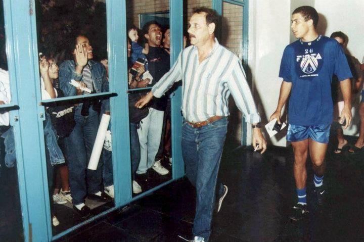 Ronaldo no Cruzeiro Brasil, Belo Horizonte, MG. 08/08/1994. O atacante Ronaldo Luís Nazário de Lima passa por corredor do Centro de Treinamento do Cruzeiro, conhecido como Toca da Raposa, enquanto fãs se exaltam do lado de fora do local, na capital mineira. Posteriormente, Ronaldo consagraria sua carreira na Europa e na Seleção Brasileira. Em 2008, o Fenômeno voltou ao Brasil para se recuperar de lesão, e acabou assinando com o Corinthians para jogar no ano seguinte. - Crédito:BETO…