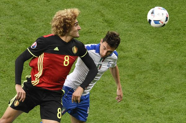 Belgium's midfielder Marouane Fellaini (R) vies for the ball against Italy's defender Matteo Darmian during the Euro 2016 group E football match between Belgium and Italy at the Parc Olympique Lyonnais stadium in Lyon on June 13, 2016. / AFP / JEAN-PHILIPPE KSIAZEK