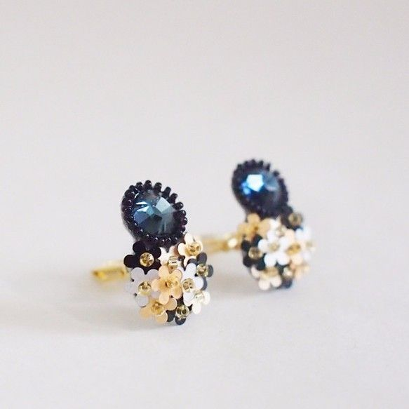 モチーフの大きさ:縦約2.0センチ×横1.5センチ(いちばん広い部分で)素材:スワロフスキービジュー、ビーズ、スパンコール、フェイクスウェード、ゴールドメッキ(イヤリング金具)澄んだ夜空のような深いブルーのスワロフスキービジューに、お花の形のスパンコールを組み合わせたイヤリングです。お花のかたちのスパンコールは、ひとつぶ約5mmの小さな小さなものを3色組合せ、ブーケのようなイメージに仕上げました。スワロフスキーのまわりには、ミクロサイズのクリスタルビーズを刺繍しています。小さなかわいらしいブーケを身に着けているような気分になれるイヤリングです。イヤリング金具はクリップ式です。ピアスはこちらからhttp://www.creema.jp/exhibits/show/id/2295659プレゼントにもおすすめです。・ピローボックスの無料ラッピング*無料ラッピングで配送方法を定形外郵便(ラッピングなし)、クリックポスト、レターパックライトをお選びの場合、厚みが規格を超えますので、ピローボックスをたたんだ状態でお送りいたします。お...