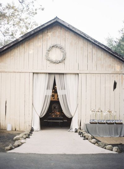 Flowy drapes dress up the entrance to this rustic barn.