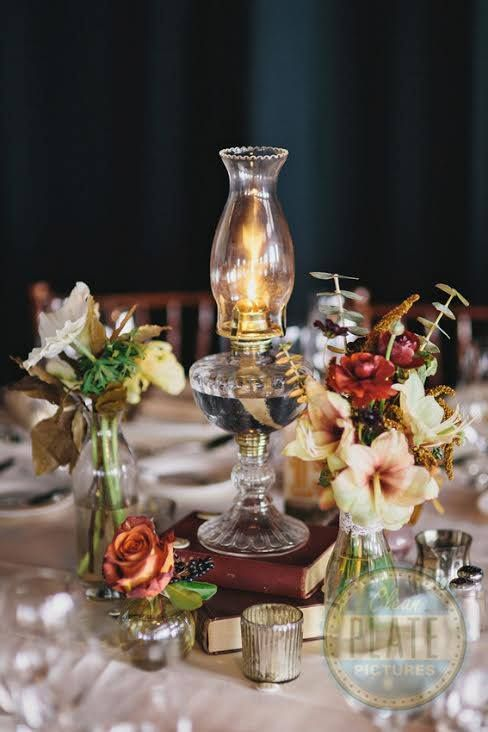 Fun fall centerpiece using an oil lamp, books, and bud vases.