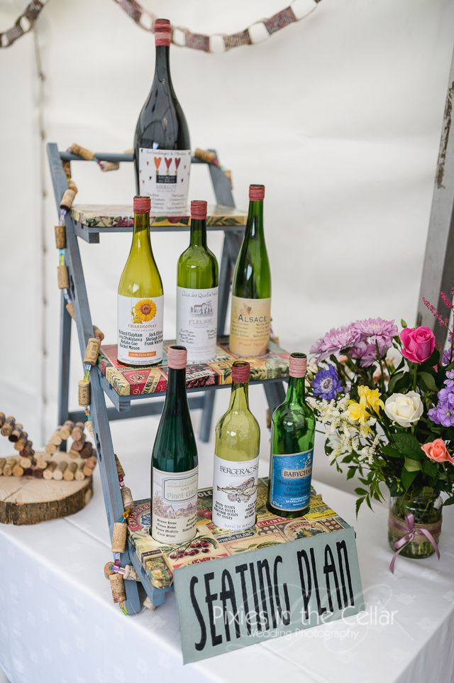 Wine bottle seating plan at this French wine themed marquee wedding reception. Went well with cork decorations too! Wedding photography by www.pixiesinthecellar.co.uk