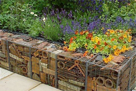"""{Here is another image of a unique Gabion Wall. The wire cages are filled with recycled terracotta pots and was featured in The Real Rubbish Garden by Claire Whitehouse at The 2005 Chelsea Flower Show in London. Image by Mark Bolton/Corbis. This is an example of functional art that is also repurposing items that would otherwise be in a landfill."""