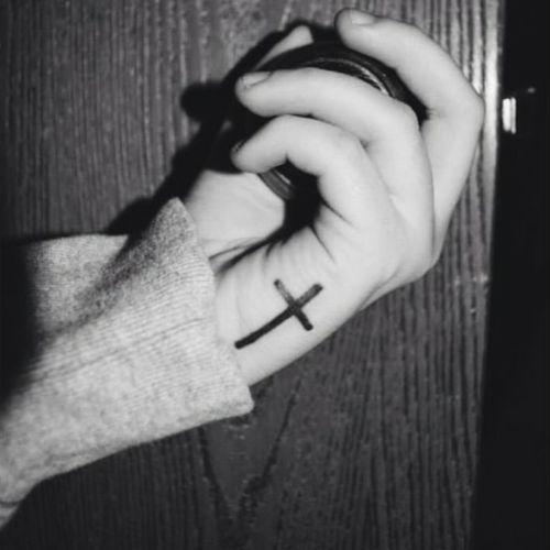 Pequeño tatuaje de una cruz en la mano de Aspen.