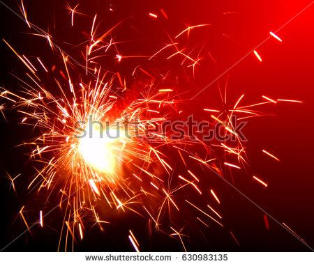 Bright sparklers on red background closeup
