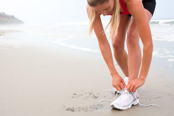 girl on beach tying shoes, ready to run. motivation