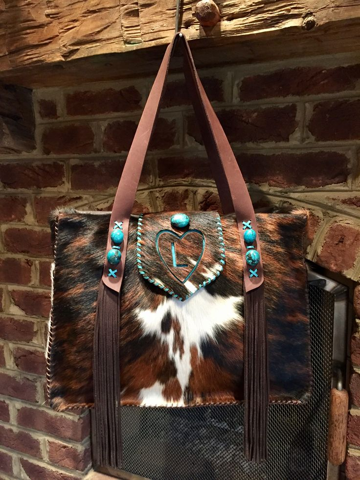 The Buckaroo Diaper Tote, with the owners initial in a heart on the flap in turquoise suede, straps with turquoise stones and strap end fringe. Custom purses and totes from gowestdesigns.us