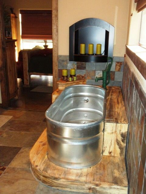 Cattle trough bathtub with antique pump as faucet