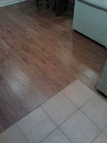 how to eliminate the toe kicker when laminate or engineered flooring meets ceramic, flooring, tile flooring, Silicone caulk to eliminate the toe kicker between the ceramic floor and the laminate