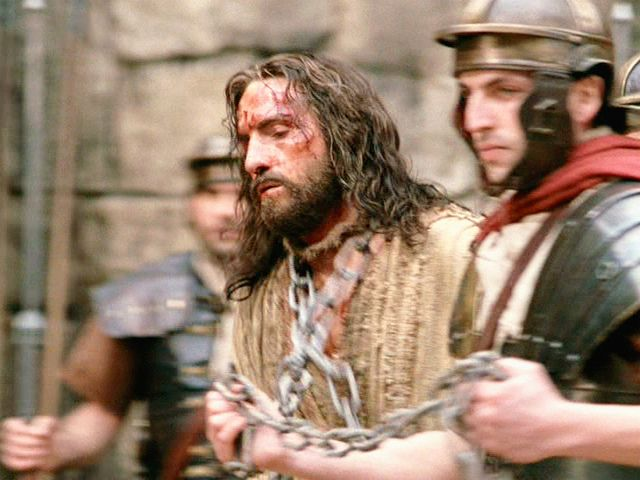 "The movie ""The Passion of the Christ"", directed by Mel  Gibson.  Seen here, James Caviezel (in center) as Jesus, in chains,  escorted by a Roman soldier.  Initial theatrical release February 25,  2004.:"