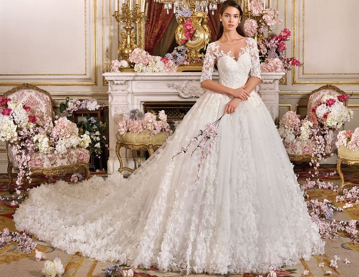 Collection Platinum Royal Romance 2018 Style DP 372 AUGASTA Princess silhouette, quarter length sleeves and illusion neckline with additions from front to back. The Tulle skirt is a real stunner with cascading 3D florals along the skirt including the cathedral train. Col. shown: ivory Available in: white, ivory