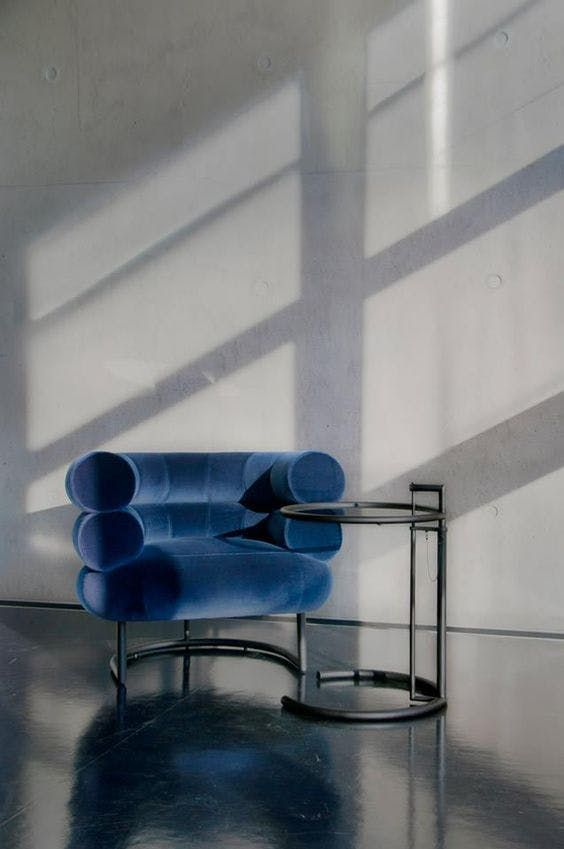 EILEEN GRAY: This is Eileen Gray's Bibendum chair, which she designed for Madame Mathieu-Levy's apartment on the Rue de Lota. It's shown here in an image from Zeeloft, alongside her adjustable E-1027 table.